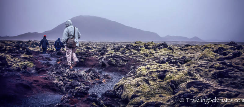 Walking on the lava field that leads to Leidarendi Lava Tube Cave, Iceland