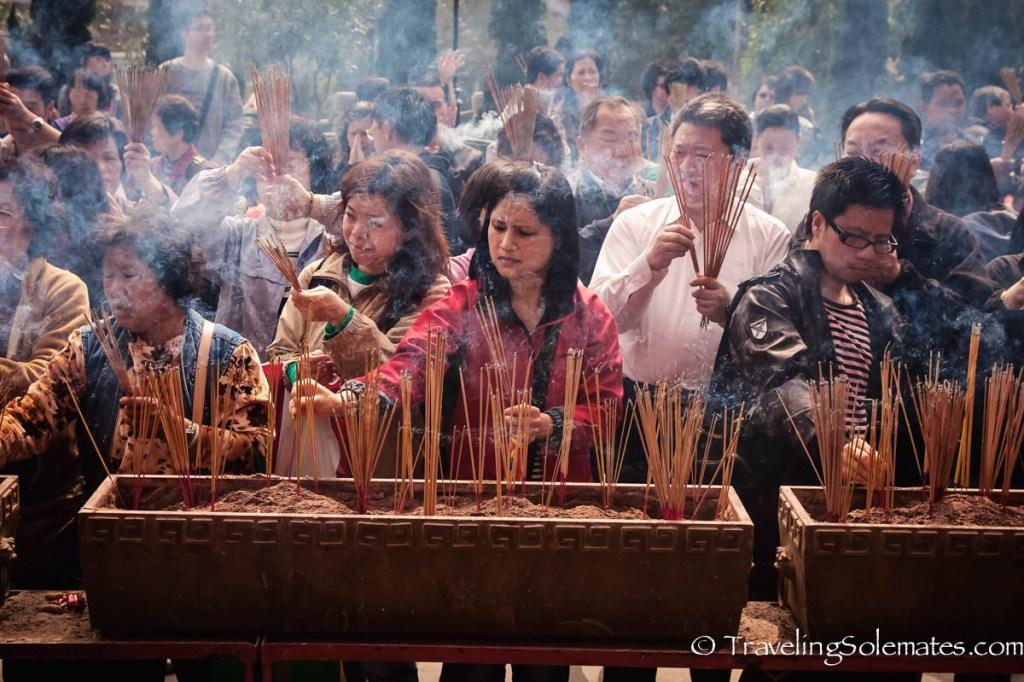 eople lighting incense in  Sik Sik Yuen Wong Tai Sin Temple in Hong Kong
