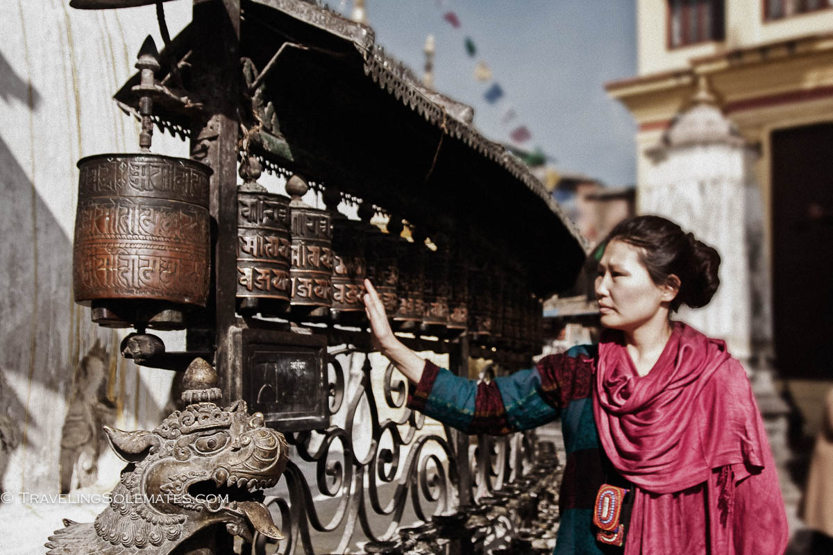 Woman spinning prayer wheels in Swayambunath, Monkey Temple, Kathmandu, Nepal