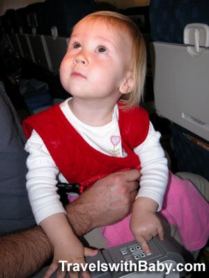 A lap-held toddler pushes Dad's buttons on a flight