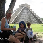 Two toddlers and a grandma keeping cool at Chichen Itza.