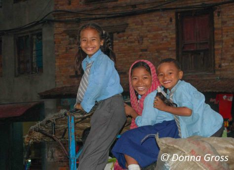 Happy school children riding atop a tractor, Bhaktapur, Nepal