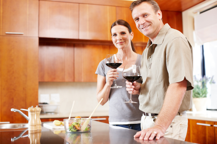 Happy mature couple smiling while standing in their kitchen and enjoying a glass of wine - portrait