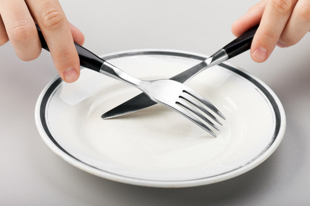 Hungry person hand holding fork knife on food plate