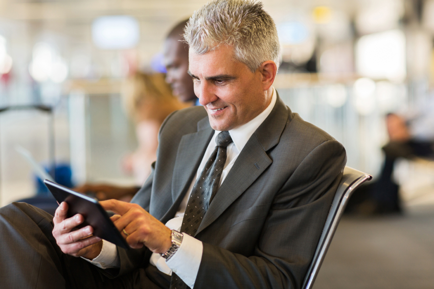 senior businessman using tablet computer while waiting for his flight at airport
