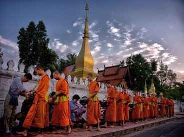 Monks at dawn in Luangprabang, Laos. The traditions of Theravada Buddhism remain strong here despite the communist government's official stance against religion. It seems tourism dollars can be more important than ideology.