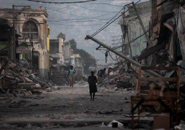 A woman walks down a devastated street in Port-au-Prince, Wednesday, Jan. 20, 2010.  A powerful 7.0-magnitude earthquake struck Haiti last week. (AP Photo/Gregory Bull)
