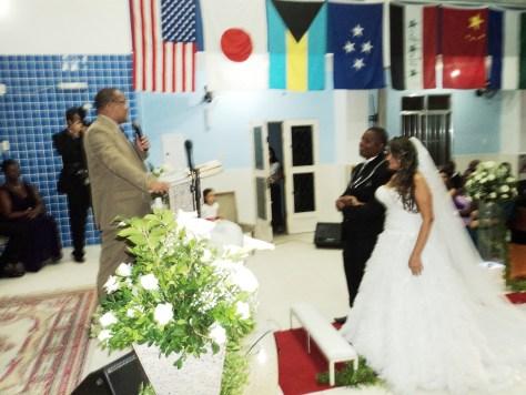 Os noivos Juliana e Paulo Junior na igreja com o pastor de celebrante.