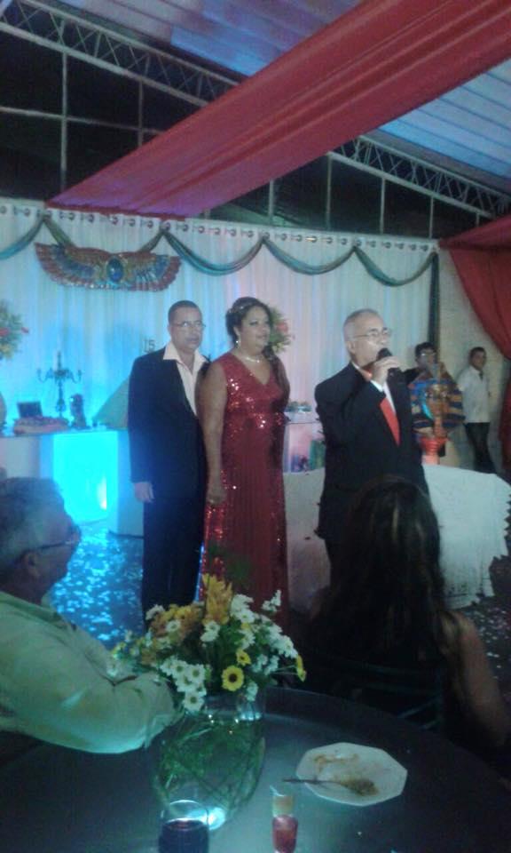 Na foto Túlio de Pinho apresentando o cerimonial com os pais da debutante atrás.