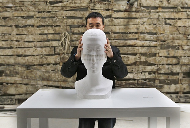 Chinese artist Li Hongbo shows his paper sculpture work, made of 6,000 pieces of paper, on the outskirts of Beijing
