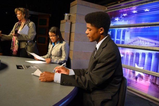 UJW mentor Donna Walker on set helping student anchors of WABJ News prep.