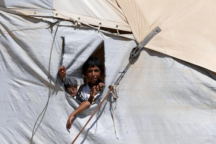 Syrian children look out of a hole in their tent in Al Zaatari refugee camp in the Jordanian city of Mafraq, close to the border with Syria, Sept. 19, 2015. Reuters
