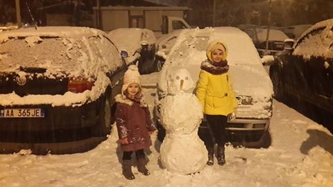 Children with a snowman in snow covered Tirana