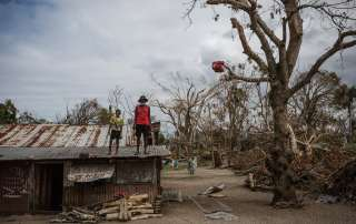 A child and an elderly man stand on the roof of a building damaged when Cyclone Pam hit Vanuatu in March 2015. Photo: UNICEF/Vlad Sokhin