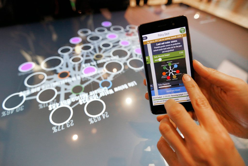 delegate plays the Hive Mind 2030 on her mobile at the Global Festival of Ideas for Sustainable Development at the World Conference Center (WCC) in Bonn, 1 March 2017.