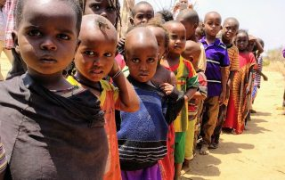 Children lining up for their one meal per day at a school in Bandarero, Northern Kenya. Photo: OCHA/ Daniel Pfister