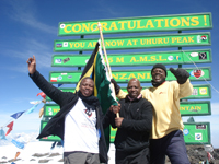 Mwasapi Kihongosi (left) and fellow Tanzanian climbers Meshack Ndaskoi, Director of Department of Gender and Development of the Ministry of Community Development Gender and Children (center) and Godfrey George Kombe, Kilimanjaro Mountain guide (right) (right) make it to the top of Mount Kilimanjaro on International Women's Day 2012. Credit: Joy Minza, KilimanjaroMountain guide
