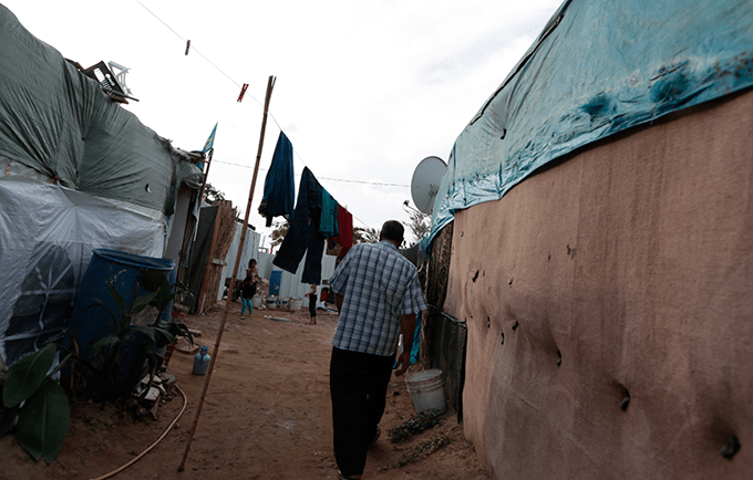 "A community leader makes his way to the tent of a pregnant 14-year-old former child bride. ""I am worried about the delivery,"" said the girl's father. © UNFPA/David Brunetti"