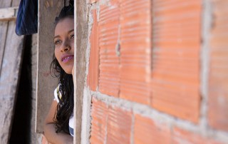 "Maria Beatriz (Bia) Teixeira dos Santos looks out the window of her home. ""I see myself as a person who is trying to change where he lives, who is fighting for what he feels is right for what is ideal for all children and adolescents,"" she says."