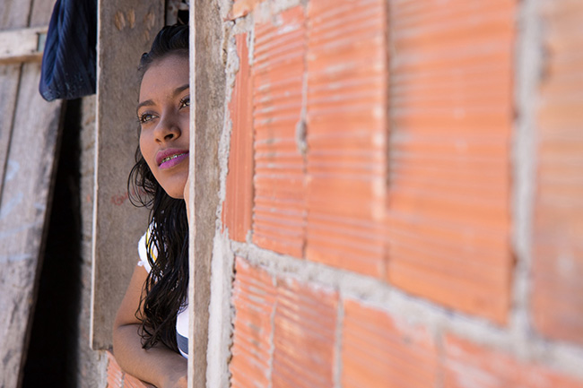 """Maria Beatriz (Bia) Teixeira dos Santos looks out the window of her home. """"I see myself as a person who is trying to change where he lives, who is fighting for what he feels is right for what is ideal for all children and adolescents,"""" she says."""