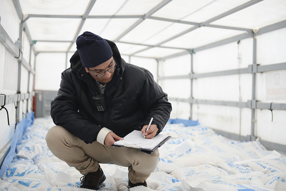 UN Volunteer Moustafa Boudria compares a cargo of humanitarian aid with a list of consignments sent by UN agencies to Syria. (Hurriyet Turkey, 2016)