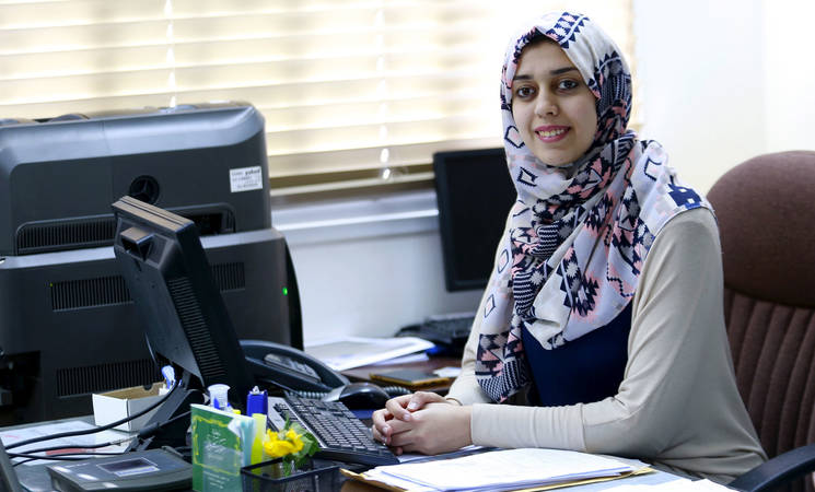 Norhan Abu Sharekh, a Palestine refugee and a Job Creation Programme beneficiary, working in the UNRWA Gaza Field Human Resources Office. © 2017 UNRWA Photo by Khalil Adwan
