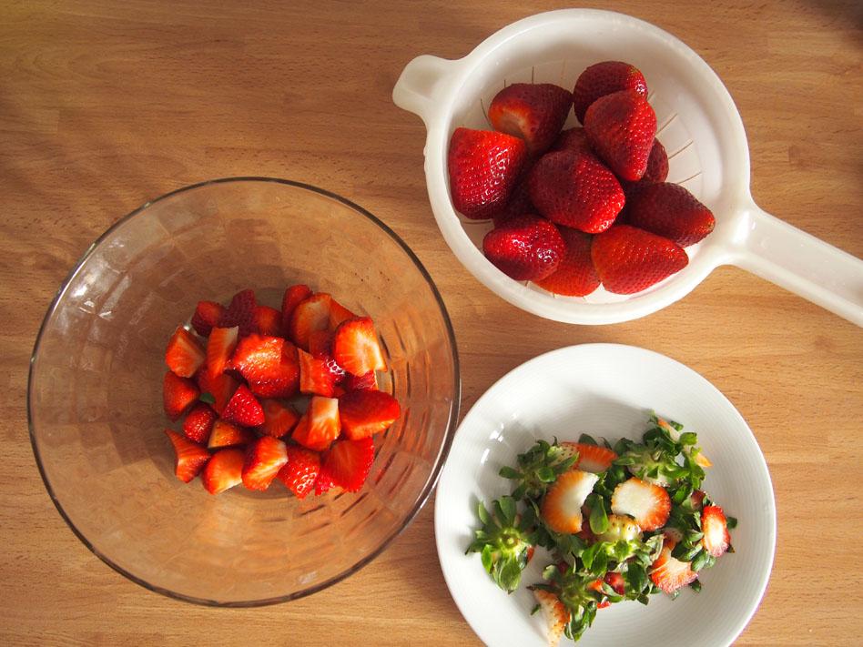 Tartaletas de fresas y chocolate blanco arreglando fresas