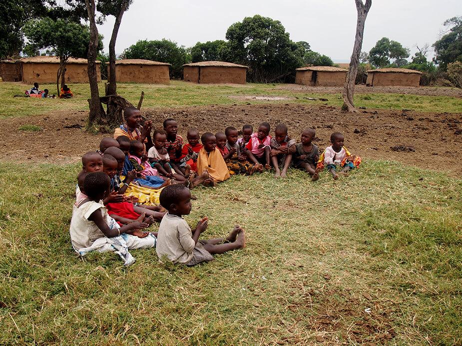 Niños masais en la aldea sentados