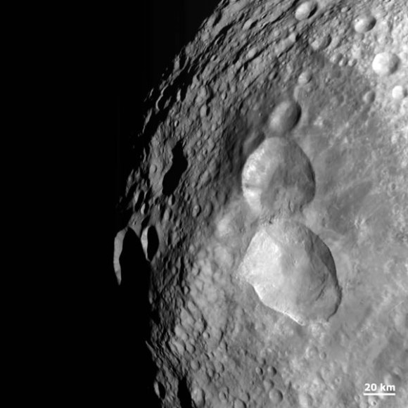 An impact structure on asteroid Vesta resembling a snowman. Credit: NASA