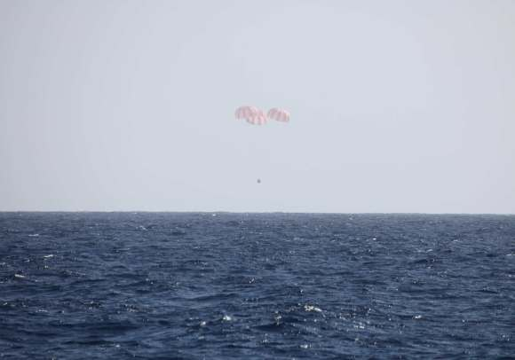 Dragon is slowed by three main parachutes prior to splashdown into the Pacific Ocean. Credit: SpaceX.