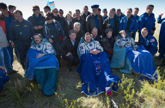 Expedition 35 Commander Chris Hadfield of the Canadian Space Agency (CSA), left, Russian Flight Engineer Roman Romanenko of the Russian Federal Space Agency (Roscosmos), center, and NASA Flight Engineer Tom Marshburn sit in chairs outside the Soyuz Capsule just minutes after they landed in a remote area outside the town of Dzhezkazgan, Kazakhstan, on Tuesday, May 14, 2013. Hadfield, Romanenko and Marshburn are returning from five months onboard the International Space Station where they served as members of the Expedition 34 and 35 crews. Photo Credit: (NASA/Carla Cioffi)