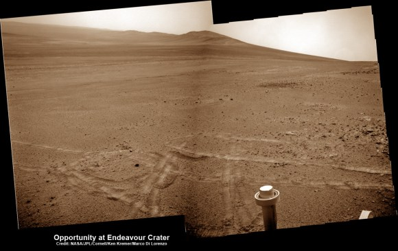 Opportunity pops a 'wheelie' on May 15, 2013 (Sol 3308) and then made history by driving further to the mountain ahead on the next day, May 16 (Sol 3309), to establish a new American driving record for a vehicle on another world.  This navcam mosaic shows the view forward to Opportunity's future destinations of Solander Point and Cape Tribulation along the lengthy rim of huge Endeavour crater spanning 14 miles (22 km) in diameter.  Credit: NASA/JPL/Cornell/Kenneth Kremer/Marco Di Lorenzo.