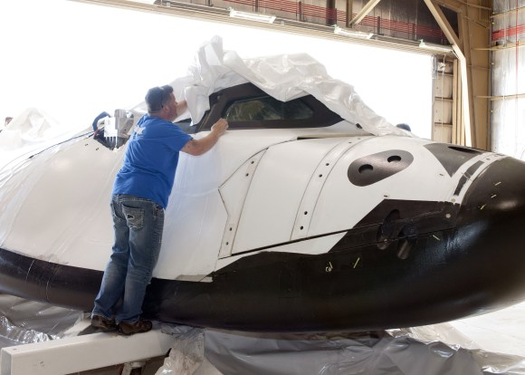 A Sierra Nevada employee removes plastic wrapping from Dream Chaser after it arrives at NASA's Dryden Flight Research Center in southern California. Credit: NASA