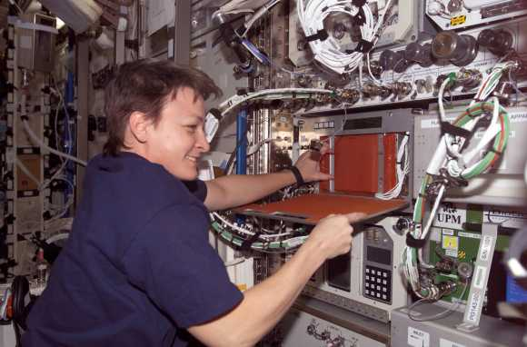 "NASA astronaut Peggy Whitson working at the Plant Generic Bioprocessing Apparatus during Expedition 5 on the International Space Station in 2002. The experiment ""monitored and maintained light, temperature, humidity and oxygen levels"", NASA stated, to look at the production of lignin (a polymer) in plants. Credit: NASA"