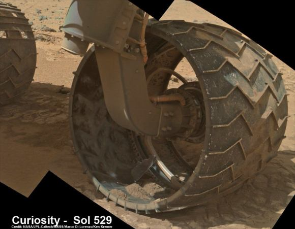 Up close photomosaic view shows lengthy tear in rover Curiosity's left front wheel caused by recent driving over sharp edged Martian rocks on the months long trek to Mount Sharp. Raw images taken by the MAHLI camera on Curiosity's arm on Jan. 31, 2014 (Sol 529) were assembled to show some recent damage to several of its six wheels   Credit: NASA / JPL / MSSS / Marco Di Lorenzo / Ken Kremer- kenkremer.com  See below complete 6 wheel mosaic and further wheel mosaics for comparison