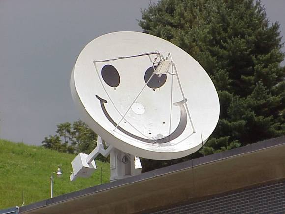 "The 4.6 meter ""smiley"" dish at the Pisgah Astronomical Research Institute, soon to be available for student use via the internet. the dish was formerly used by the military, and the ""face"" was used to taunt any spy satellites passing overhead! (Credit:  SETI League photo used by permission under SETI's fair use policy)."
