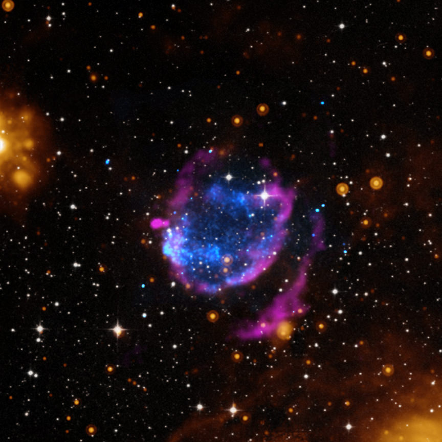 The supernova remnant G352.7-0.1 in a composite image with X-rays from the Chandra X-Ray Telescope (blue), radio waves from the Very Large Array (pink), infrared information from the Spitzer Space Telescope (orange) and optical data from the Digital Sky Survey (white). Credit: X-ray: NASA/CXC/Morehead State Univ/T.Pannuti et al.; Optical: DSS; Infrared: NASA/JPL-Caltech; Radio: NRAO/VLA/Argentinian Institute of Radioastronomy/G.Dubner