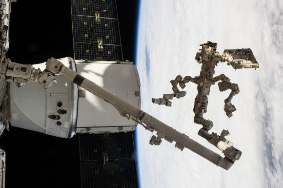 "Backdropped against a cloudy portion of Earth, Canada's Dextre robotic ""handyman"" and Canadarm2 dig out the trunk of SpaceX's Dragon cargo vessel docked to the ISS after completing a task 225 miles above the home planet.  Credit: NASA"