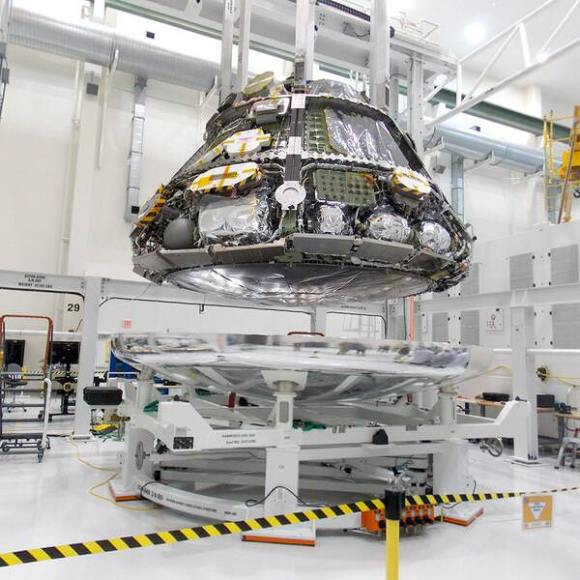 Coming together! Orion's heat shield and crew module in position for mating operations at NASA KSC. Credit: NASA