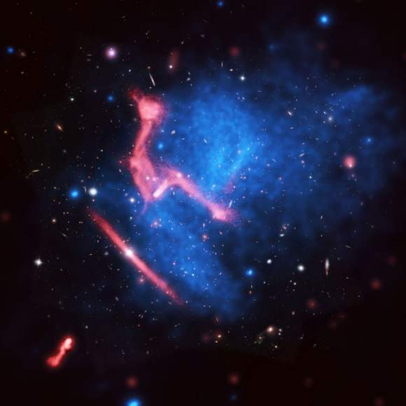 Galaxy clusters MACS J0717+3745 colliding about five billion light-years away from Earth. This is a composite image of visible light from the Hubble Space Telescope (background), X-ray data from the Chandra X-Ray Observatory (blue) and radio waves from the Very Large Array (red).Credit: Van Weeren, et al.; Bill Saxton, NRAO/AUI/NSF; NASA