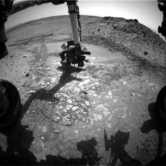 "This image from the front Hazcam on NASA's Curiosity Mars rover shows the rover's drill in place during a test of whether the rock beneath it, ""Bonanza King,"" would be an acceptable target for drilling to collect a sample. Subsequent analysis showed the rock budged during the Aug. 19, 2014, test. Credit: NASA/JPL-Caltech"