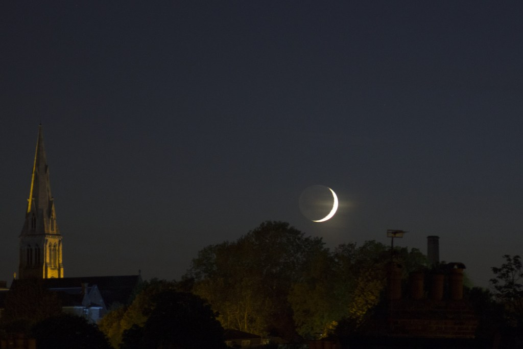 A waxing crescent Moon+Earthshine setting over southwest London. Image credit and copyright: Roger Hutchinson