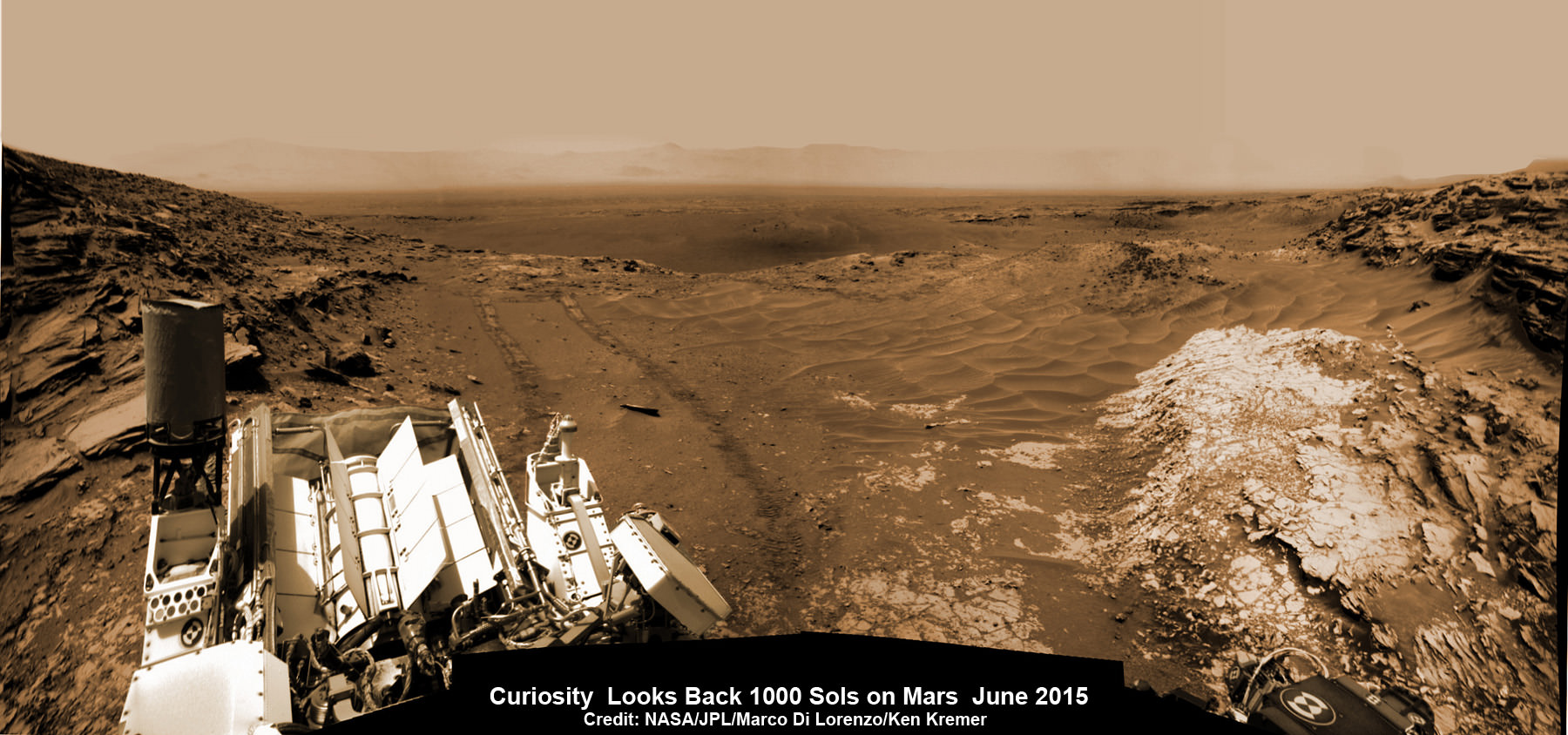NASA's Martian Curiosity rover looks backs to 1000 Sols of science and exploration on the surface of the Red Planet.  Robot wheel tracks lead back through valley dunes.  Gale Crater rim seen in the distant hazy background.  Sol 997 (May 28, 2015) navcam camera raw images stitched and colorized. Credit:  NASA/JPL-Caltech/ Marco Di Lorenzo/Ken Kremer/kenkremer.com