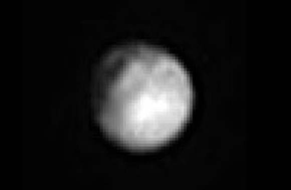 """Pluto with its enigmatic """"crater"""" photographed on June 27. The apparent row of three depressions near the bottom of the globe are most likely artifacts from processing. Credit:"""