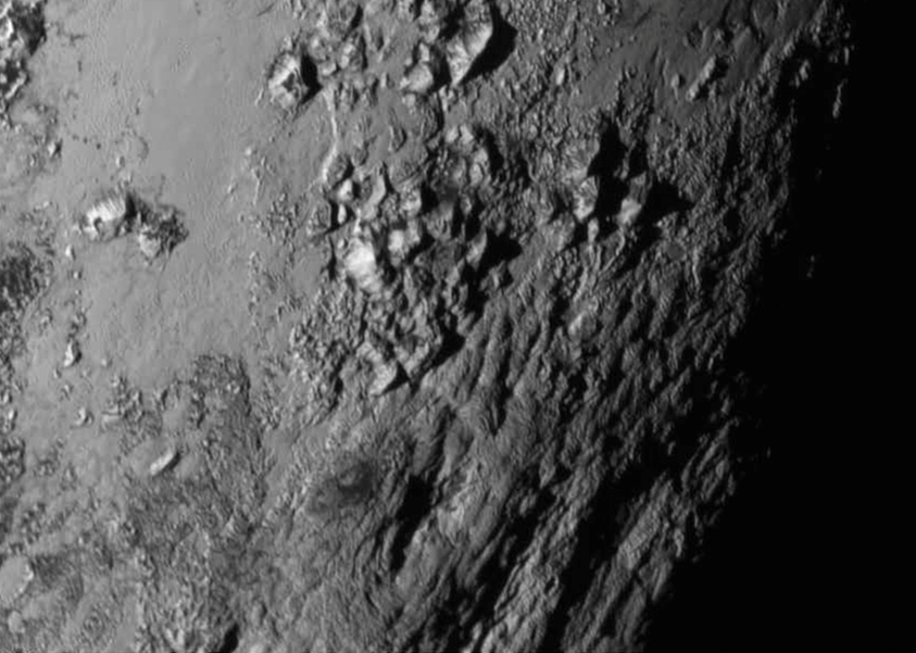New close-up images of a region near Pluto's equator reveal a giant surprise -- a range of youthful mountains rising as high as 11,000 feet (3,500 meters) above the surface of the icy body.  Credits: NASA/JHU APL/SwRI