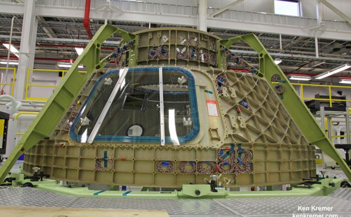 View of upper dome and newly attached crew access tunnel of the first Boeing CST-100 'Starliner' crew  spaceship under assembly at NASA's Kennedy Space Center.   This is part of the maiden Starliner crew module known as the Structural Test Article (STA) being built at Boeing's refurbished Commercial Crew and Cargo Processing Facility (C3PF) manufacturing facility at KSC. Numerous strain gauges have been installed for loads testing. Credit: Ken Kremer /kenkremer.com