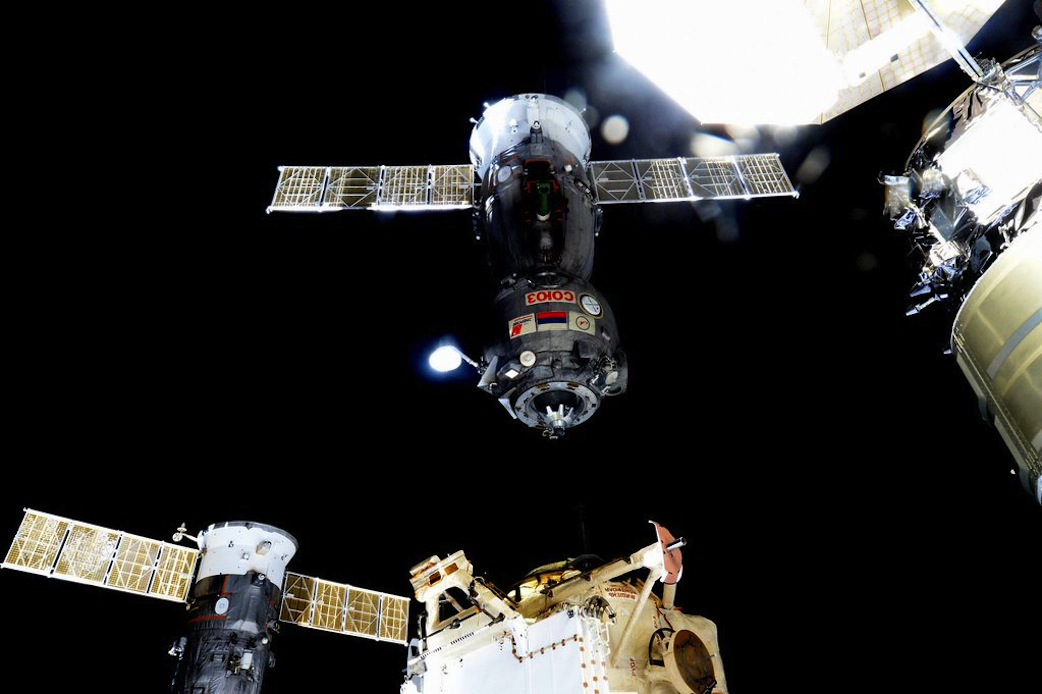 Expedition 46 Commander Scott Kelly of NASA captured this image, from aboard the International Space Station, of the Dec. 11, 2015 undocking and departure of the Soyuz TMA-17M carrying home Expedition 45 crew members Kjell Lindgren of NASA, Oleg Kononenko of the Russian Federal Space Agency and Kimiya Yui of the Japan Aerospace Exploration Agency after their 141-day mission on the orbital laboratory. Newly arrived Cygnus cargo ship and solar panels seen at upper right. Credits: NASA/Scott Kelly