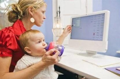 donna che lavora al computer che tiene sulle ginocchia un bambino a cui tiene il biberon