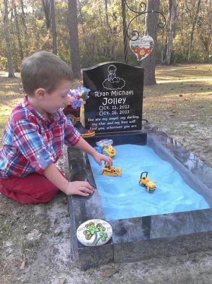 bimbo gioca sulla tomba del fratello