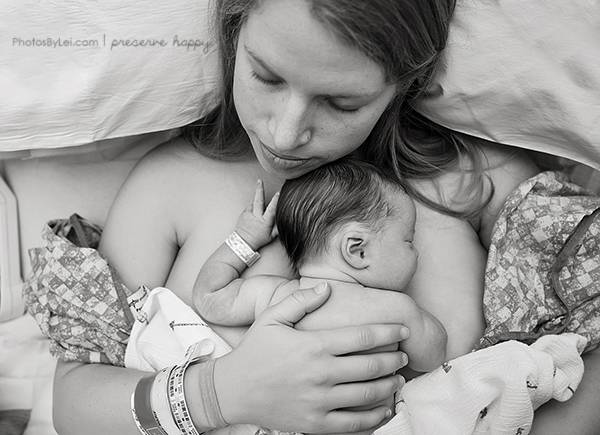 Mom and baby having skin to skin after a hospital c-section, and baby gives the peace sign.